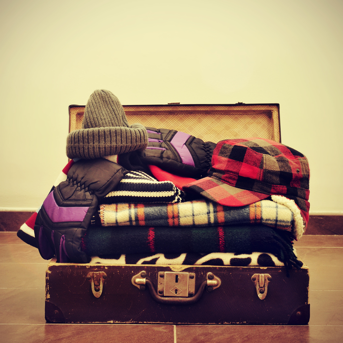 a pile of warming clothes, such as gloves, caps or blankets, in an old suitcase, with a retro effect