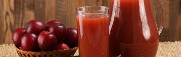 plum juice in a glass and pitcher