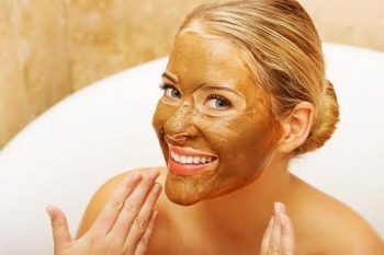 Portrait of a happy woman showing her face with chocolate mask